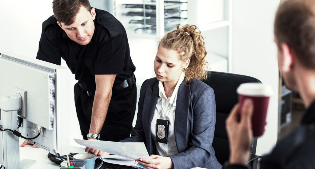 Two law enforcement officers review a paper accreditation file.