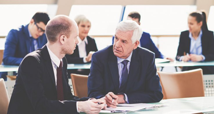 Two government workers discuss an issue at a table.