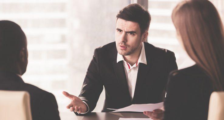 man speaking in board meeting