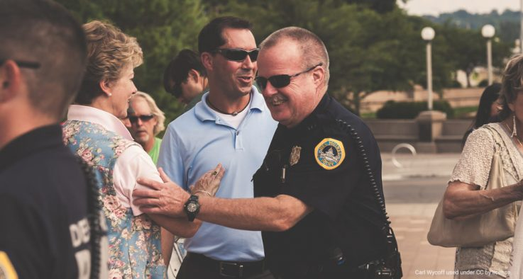 Police officer greets members of the community at an outdoor event.