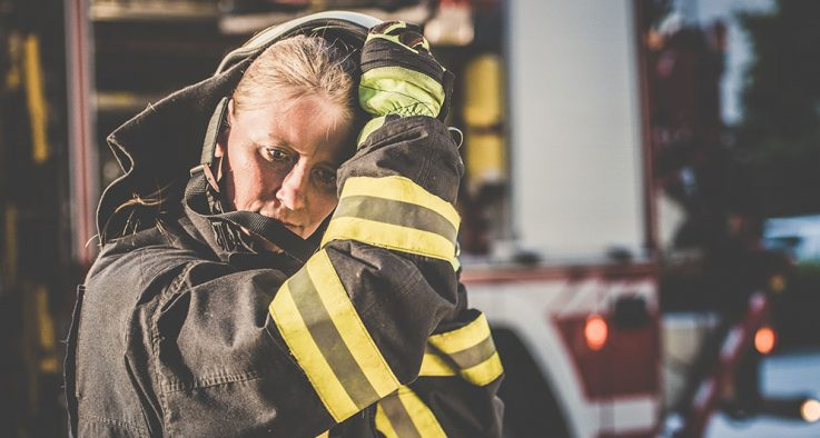 firewoman removing her helmet