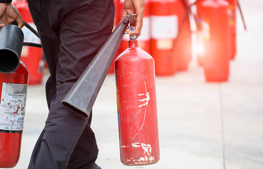 fireman carrying fire extinguishers