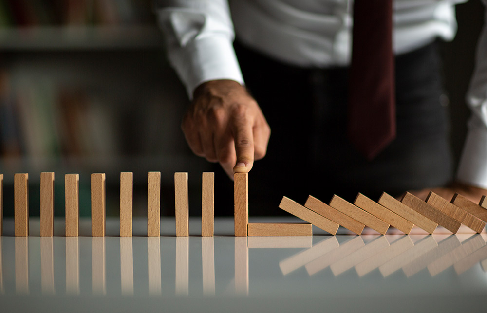 businessman with finger on domino