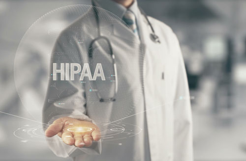 Doctor holding the word HIPAA in his hand