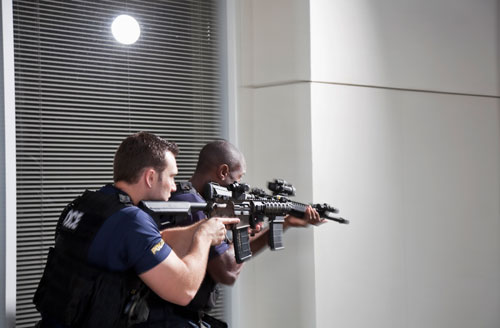 two police officers entering building with rifles