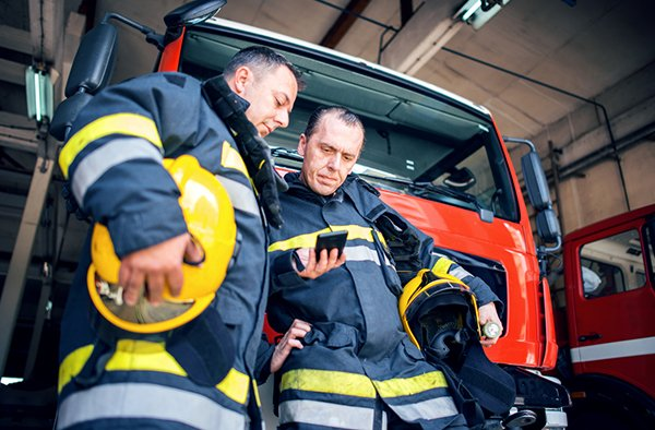 firemen looking at policies on smartphone
