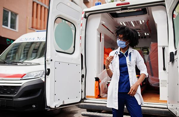 EMS worker behind ambulance